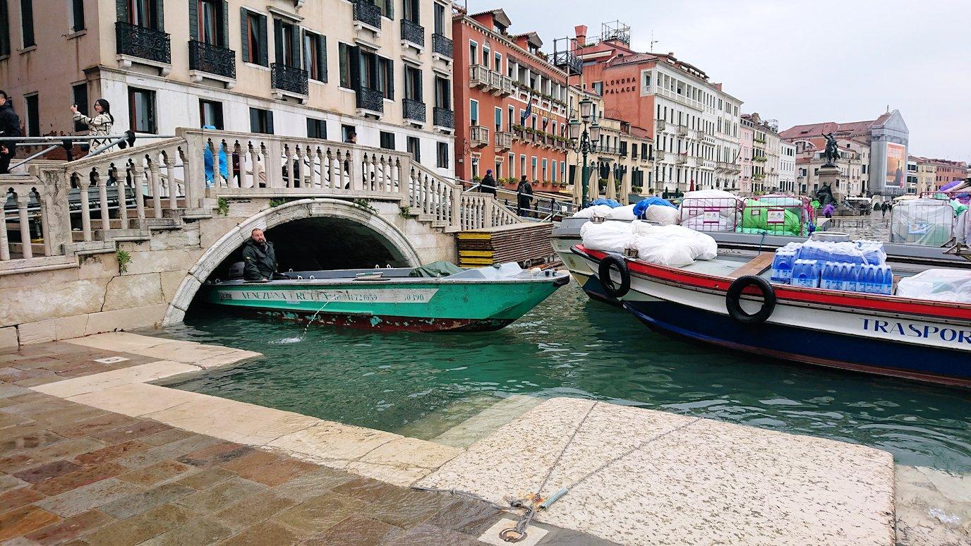 浸水するベネチアの街の橋の下を通る船