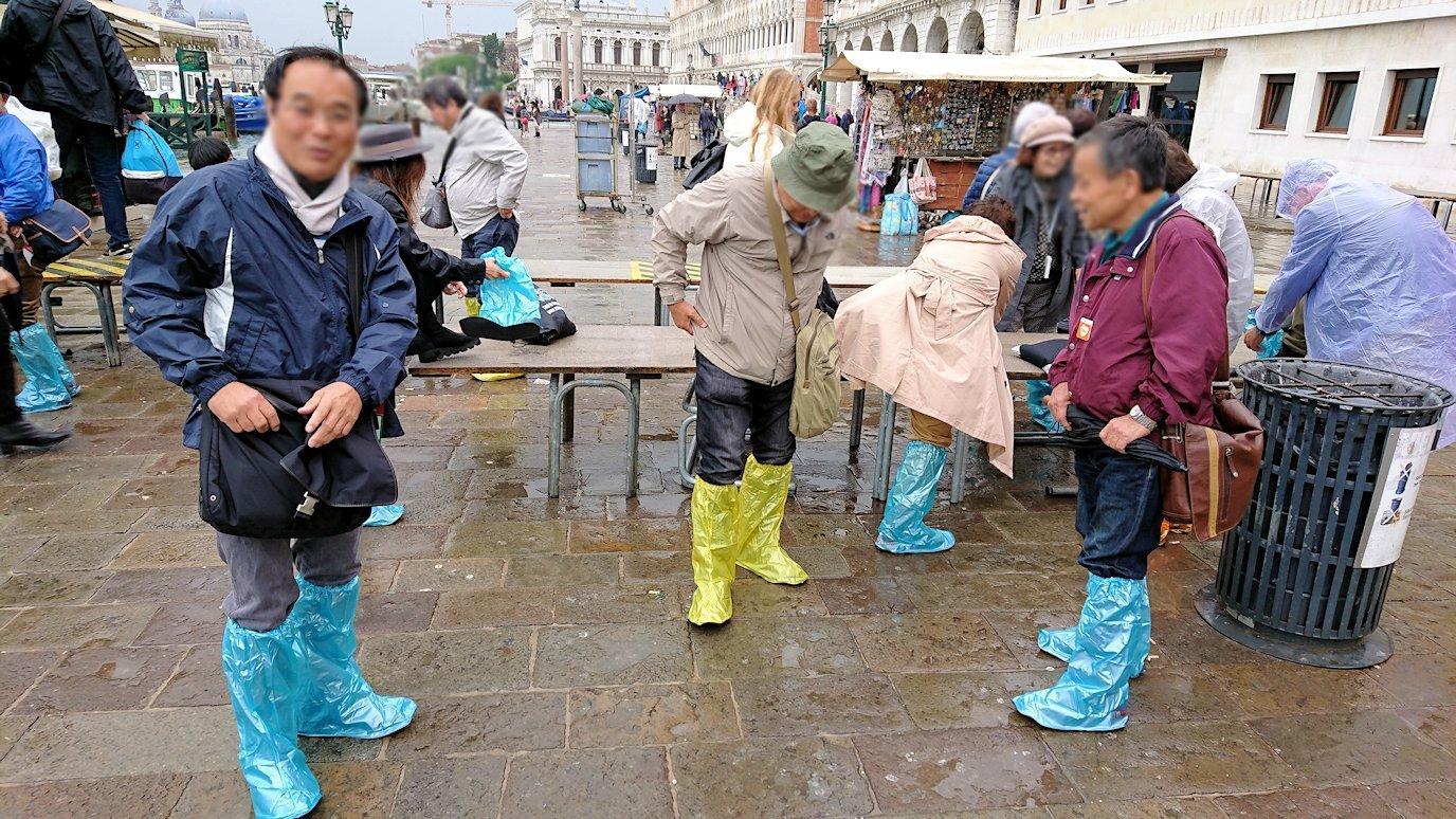 ベネチアの街で靴カバーを装着する人々