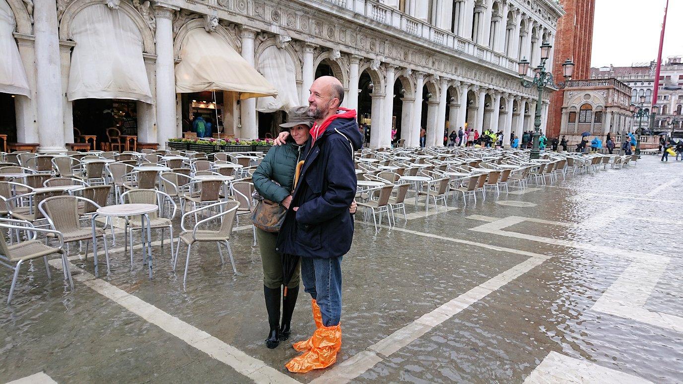 ベネチアのサンマルコ広場で冠水している広場で記念撮影するカップル