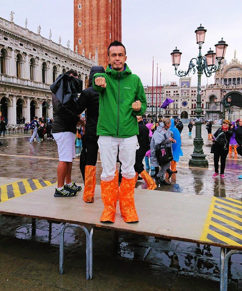 ベネチアのサンマルコ広場で冠水している広場で鐘楼をバックに記念撮影