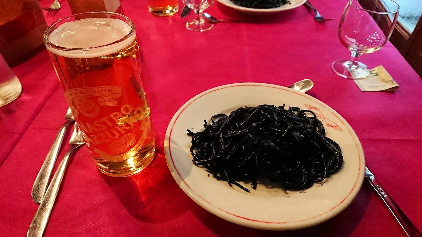 ベネチアの街のレストランのイカ墨パスタとビール