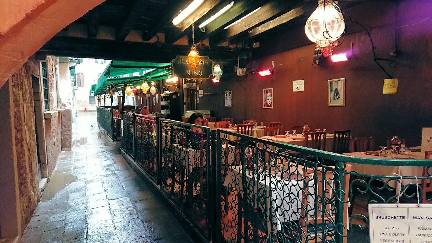 ベネチアの街の路地にあるレストランのテラス席