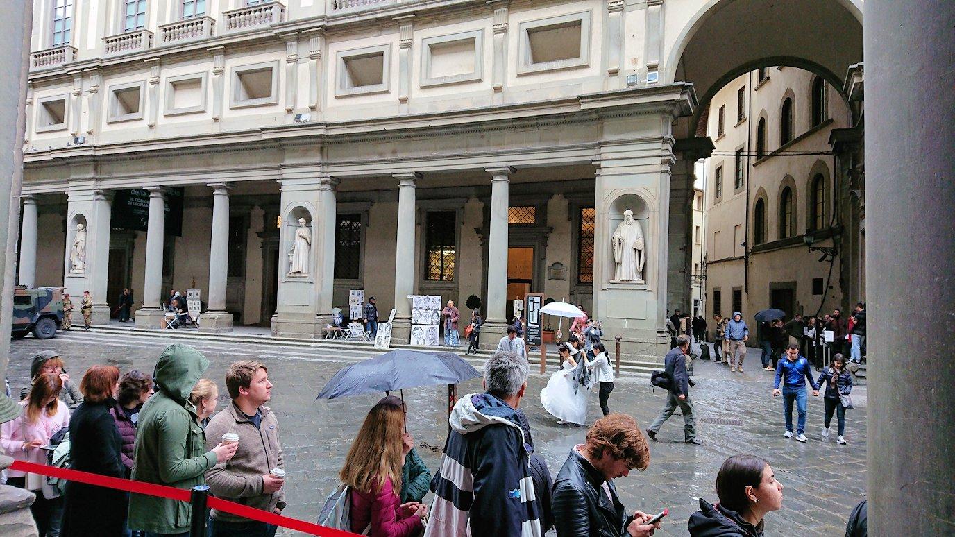ウフィツィ美術館前の行列前で結婚写真を撮るカップル