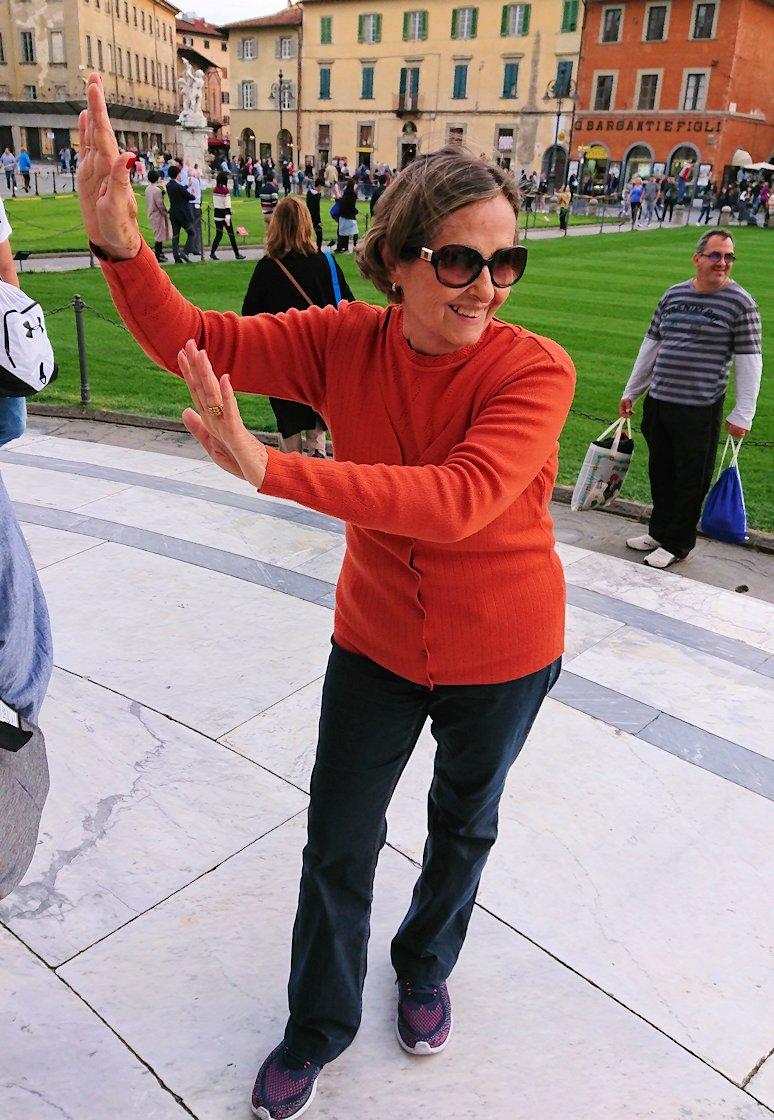 ピサの斜塔の前でポージングするおばあちゃんのアップ写真