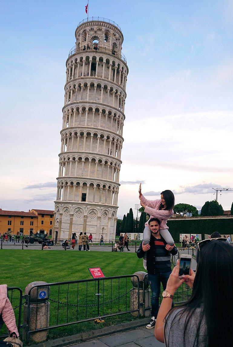 ピサの斜塔前で記念撮影する人達