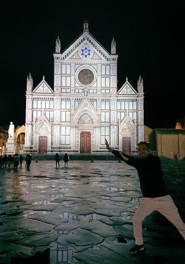 フィレンツェの夜のサンタクローチェ教会の正面でポーズ