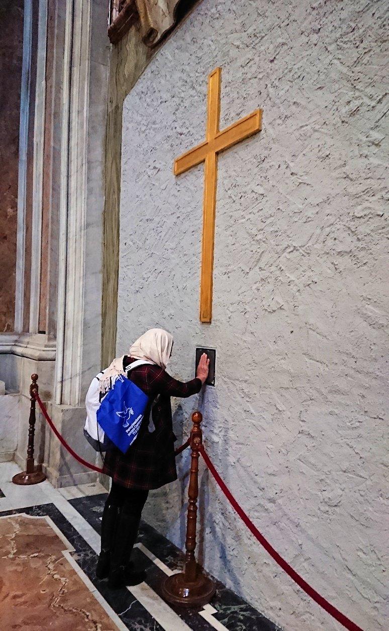 サンピエトロ大聖堂の構内の十字架に触れる人