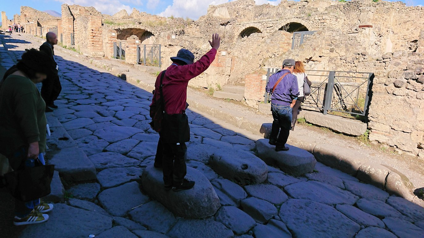 ポンペイ遺跡の道の石を手を挙げて渡る