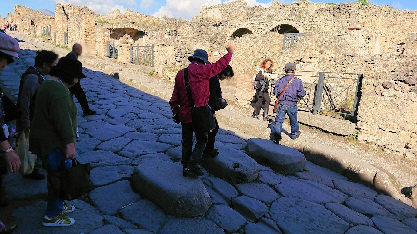 ポンペイ遺跡の道の石を手を挙げて渡る2
