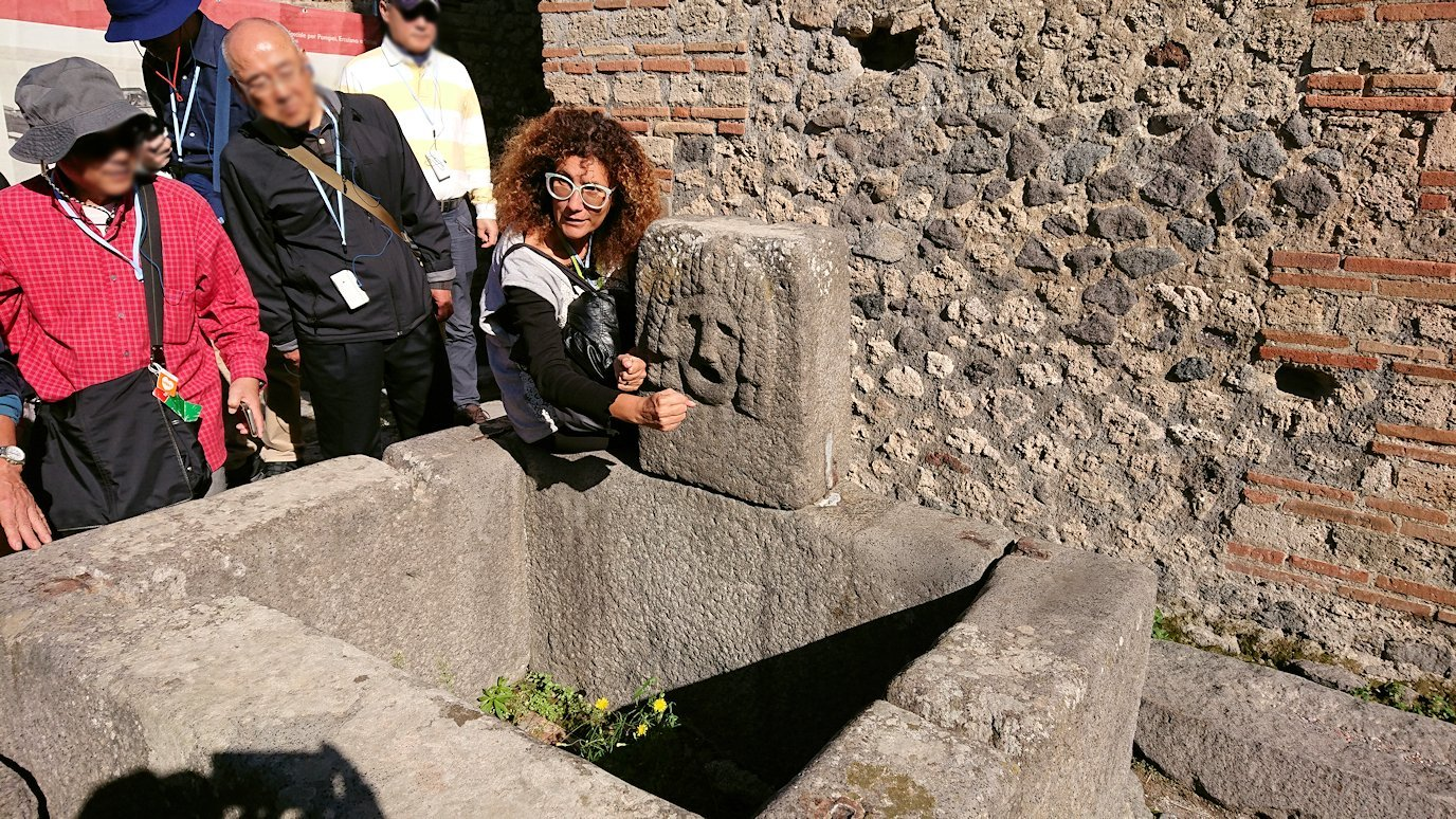 ポンペイ遺跡の手洗い場で説明