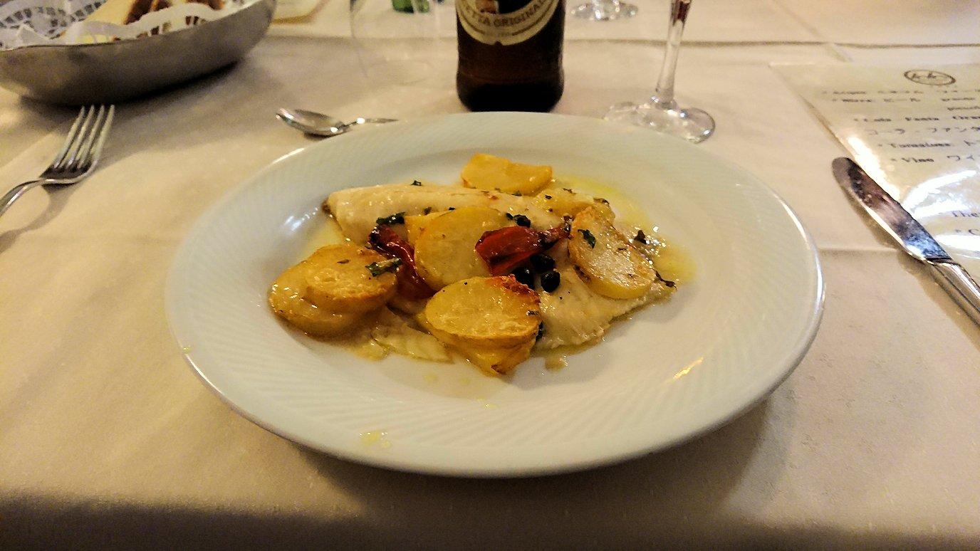 アルベロベッロのホテルの夕食会場で白身魚を食べる