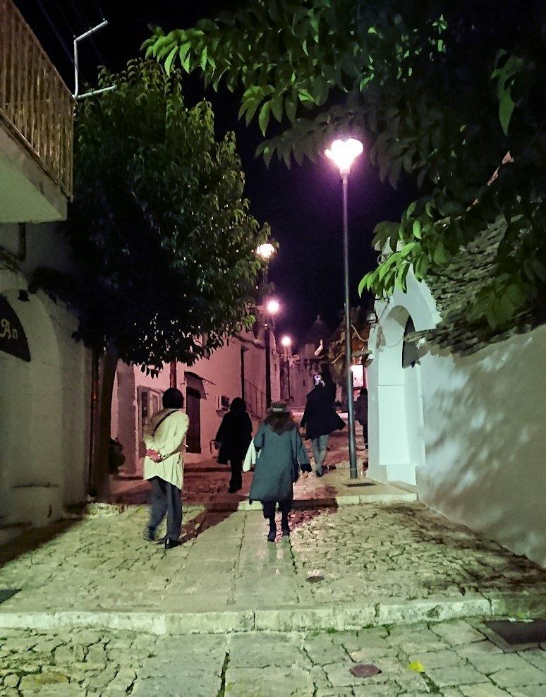 夜のアルベロベッロのモンティ地区のトゥルリ前の道をのぼる
