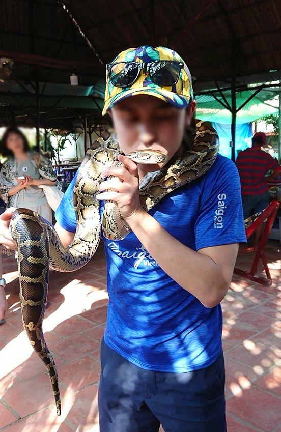 メコン川クルーズの島で蛇の首巻を体験する岡ちゃん