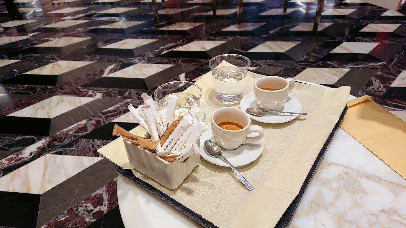 ローマの空港の国際線ターミナルのグッチでコーヒーを飲む
