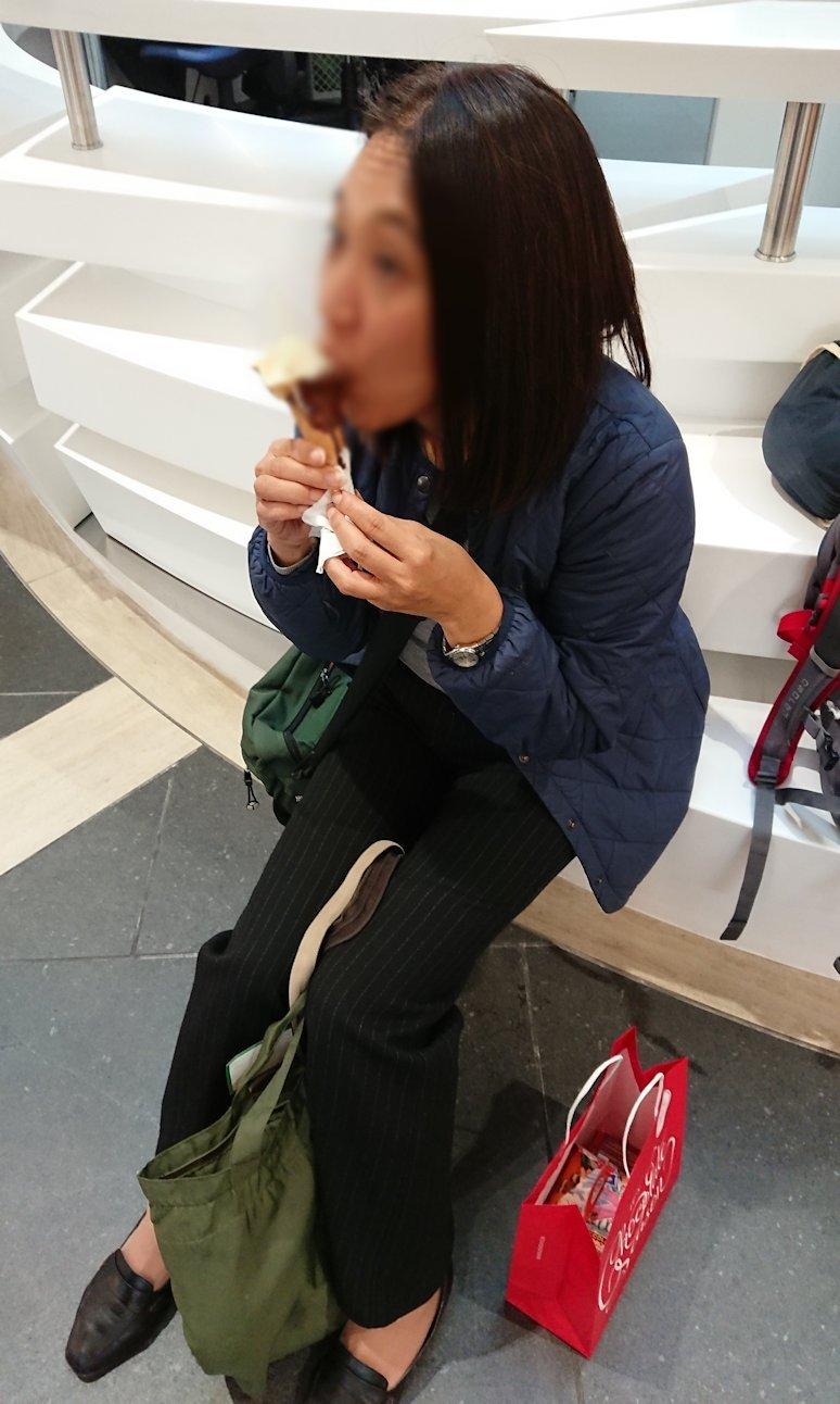 ローマ空港内の案内所前でチョコレートを食べて油断する添乗員さん