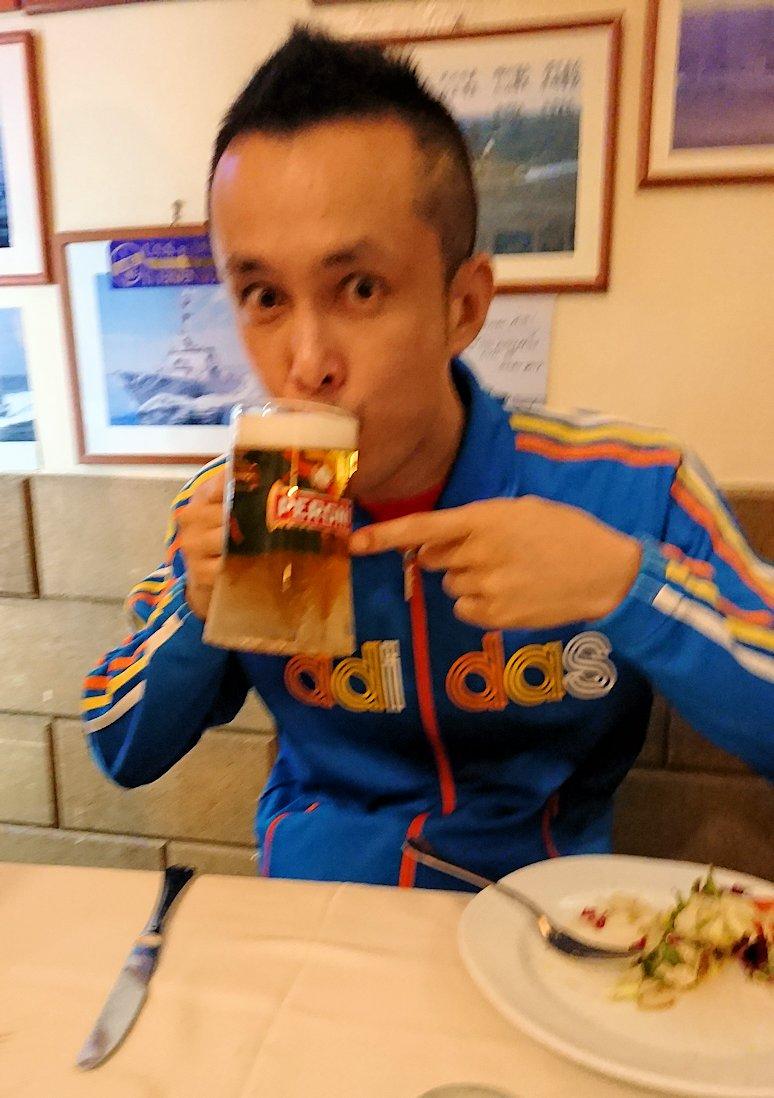 ナポリの街のレストランのビールを飲む男