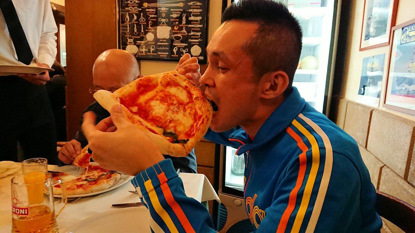 ナポリの街のレストランで美味しいピザを食べる男