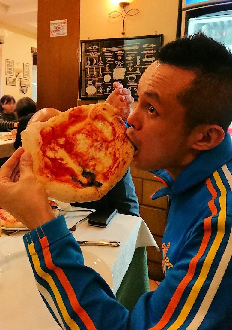 ナポリの街のレストランで美味しいピザを食べる男2