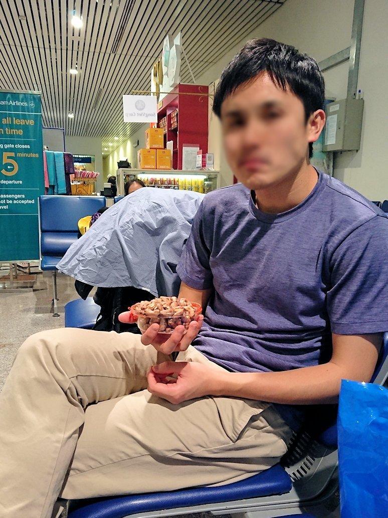 タンソンニャット国際空港の搭乗ゲート付近でナッツを食べる