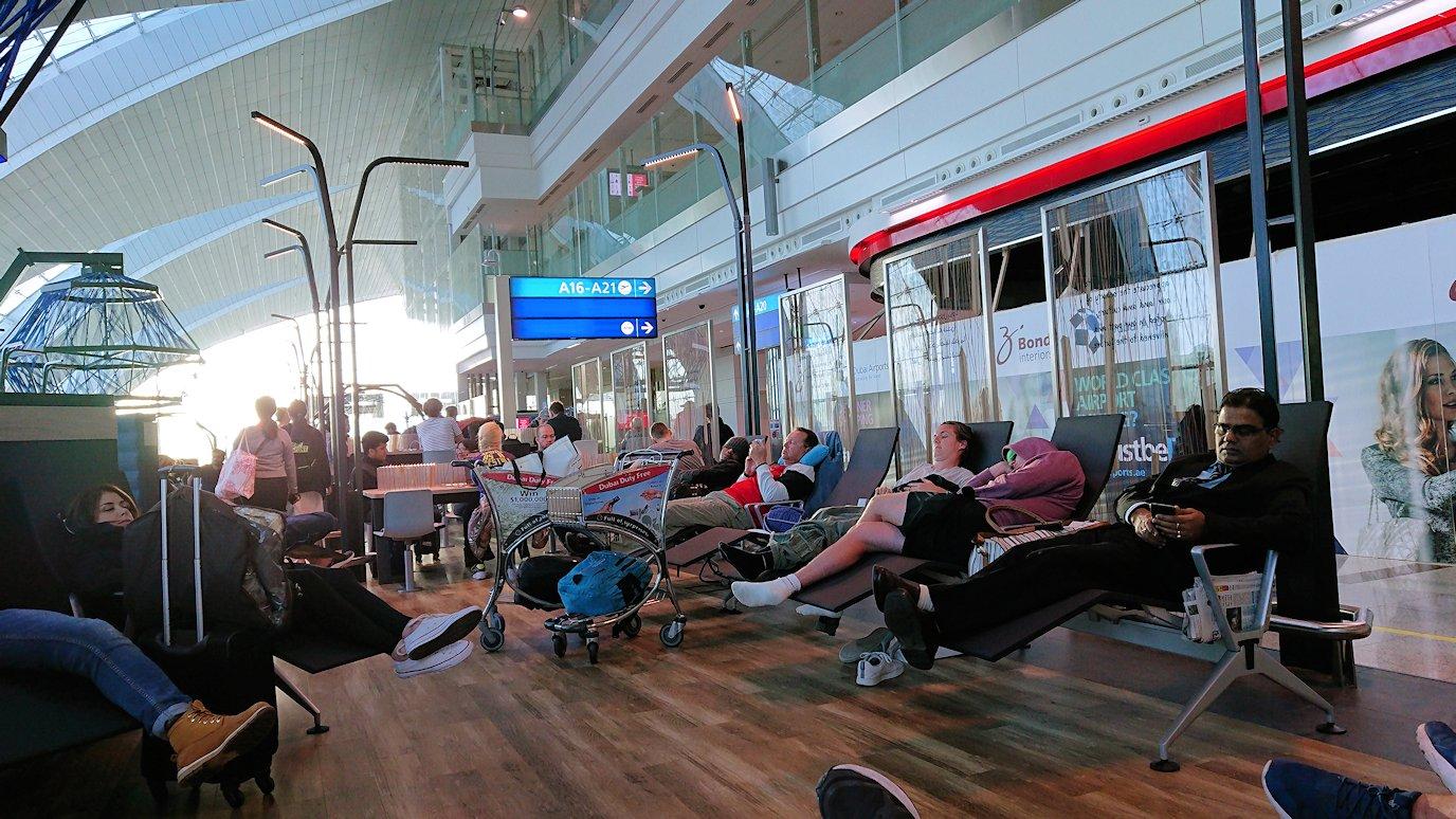 ドバイ空港内で彷徨う人々が集まるベンチで寝るひと