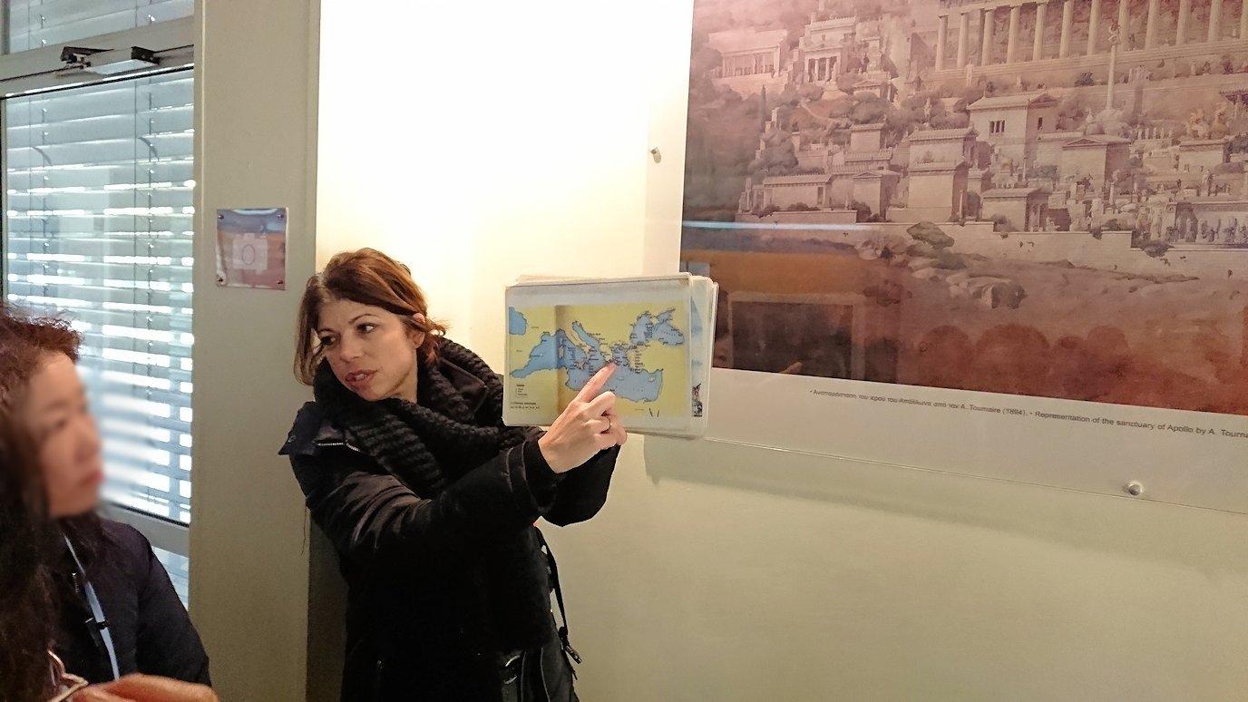 デルフィ遺跡の博物館内でガイドさんからレクチャーを受ける