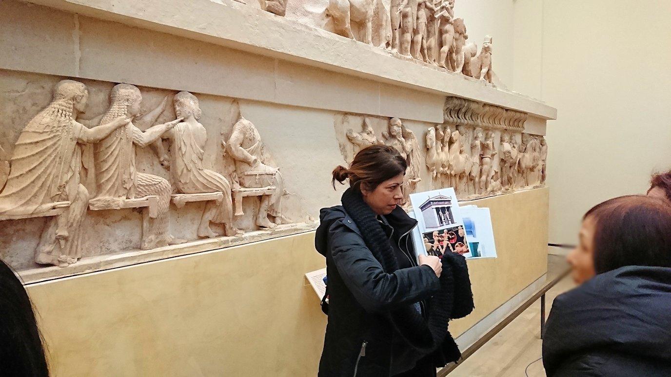 デルフィ遺跡の博物館内のレリーフを見ながら説明