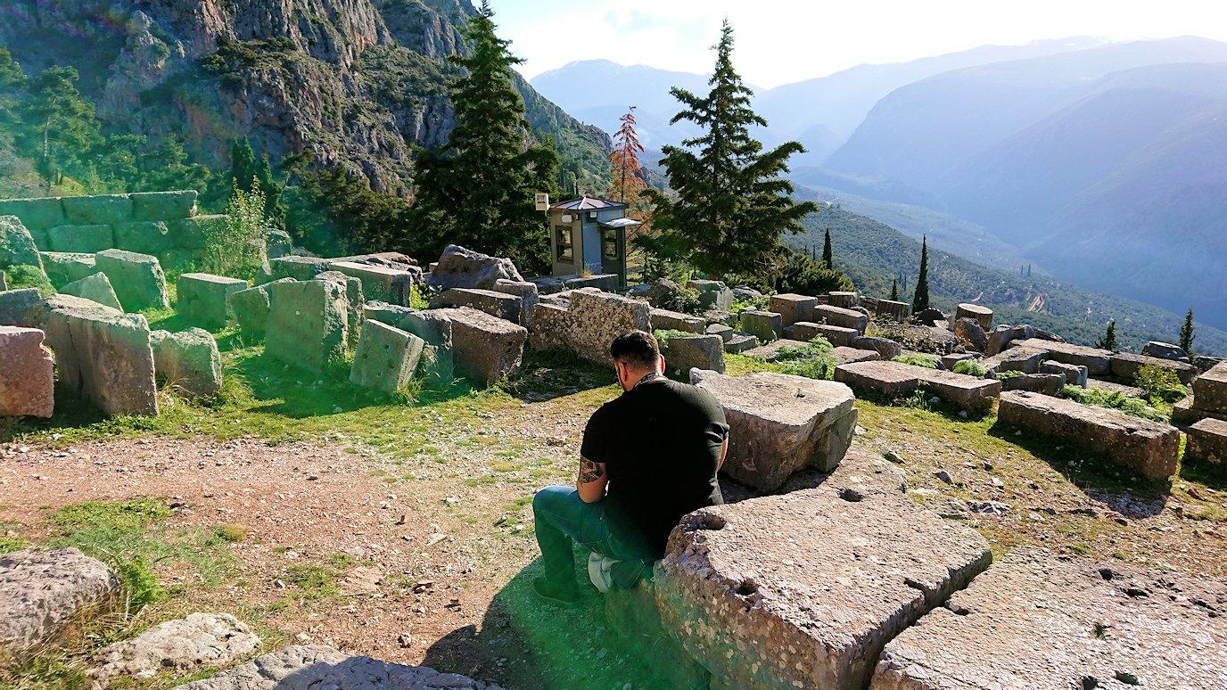デルフィ遺跡でアポロン神殿を見上げる途中に座る男性の姿