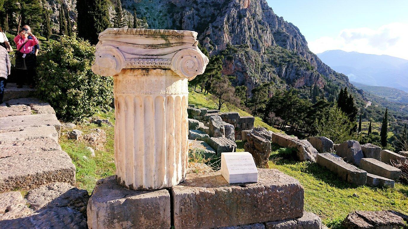 デルフィ遺跡でアポロン神殿を見上げる途中に座る男性の姿2