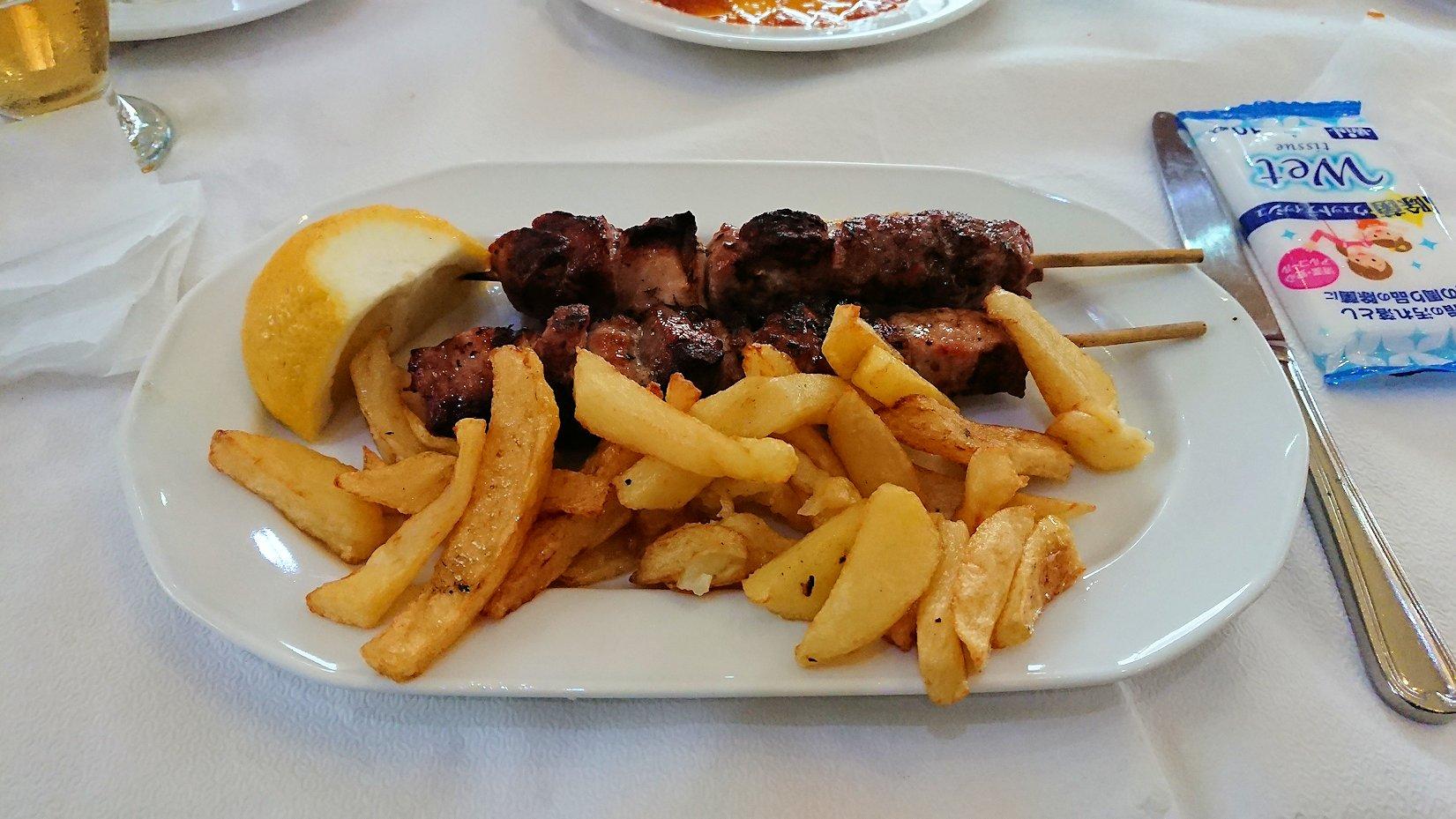ギリシャのディアコフトのレストランのメイン料理 スブラキを食べる
