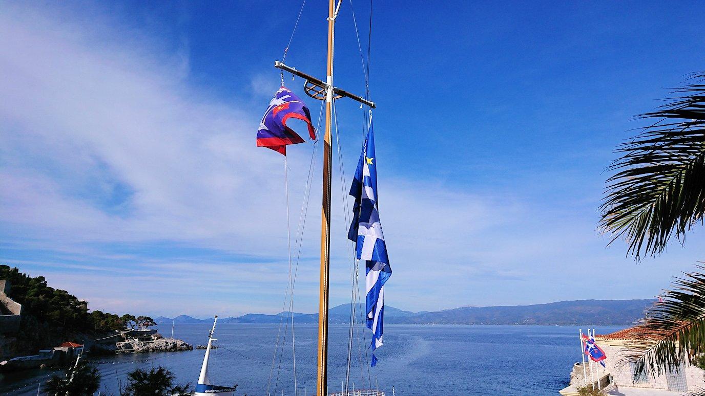 エーゲ海のイドラ島の高台になびくギリシャ国旗を見る