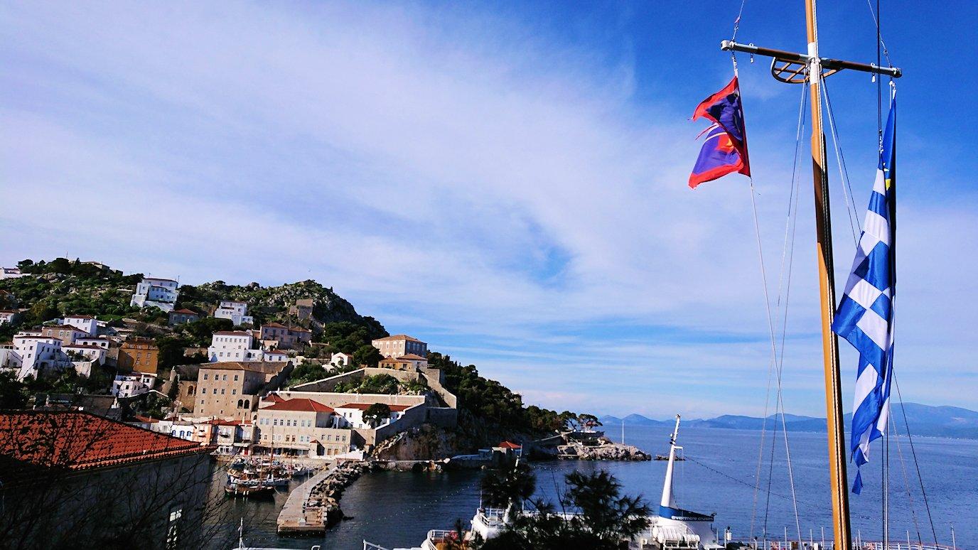 エーゲ海のイドラ島の高台になびくギリシャ国旗を見る2