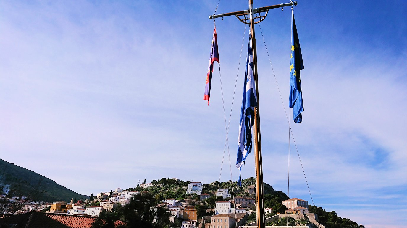 エーゲ海のイドラ島の高台になびくギリシャ国旗を見る3