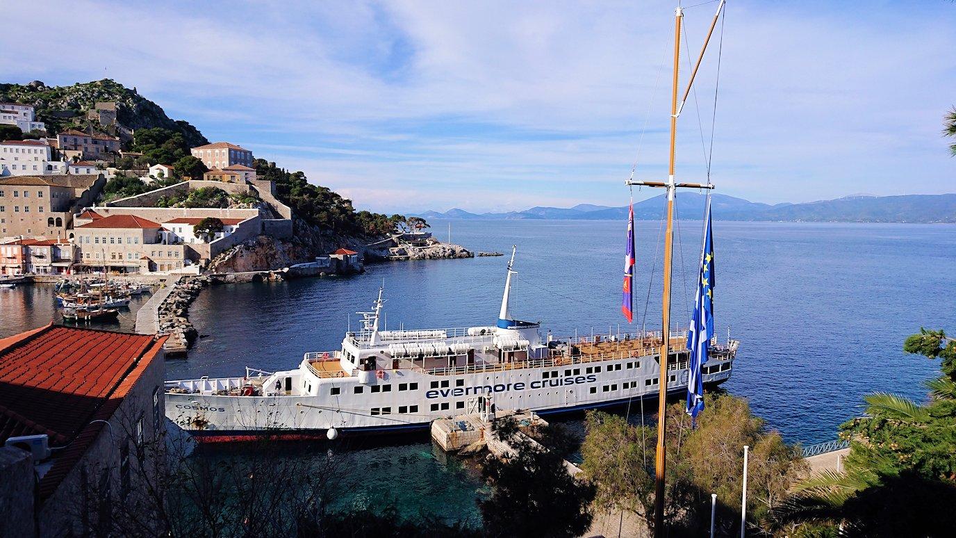 エーゲ海のイドラ島の高台になびくギリシャ国旗を見ながら