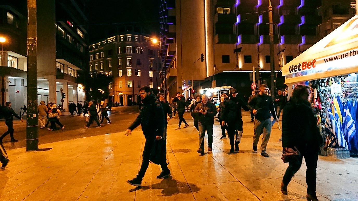 アテネの夜にシンタグマ広場付近で人々が逃げ惑う