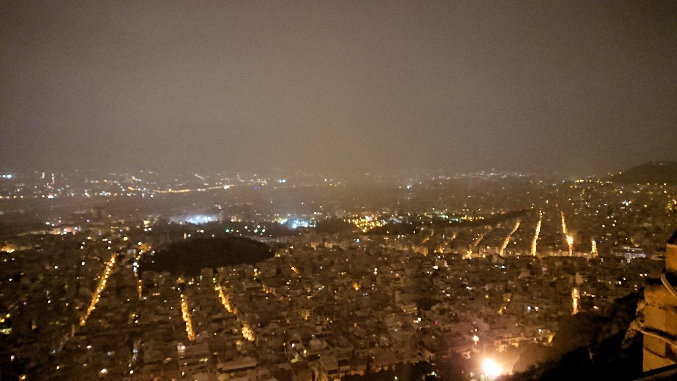 アテネの夜にリカヴィトスの丘からケーブルカーに乗って頂上に到着しアテネ市内を見回す様子