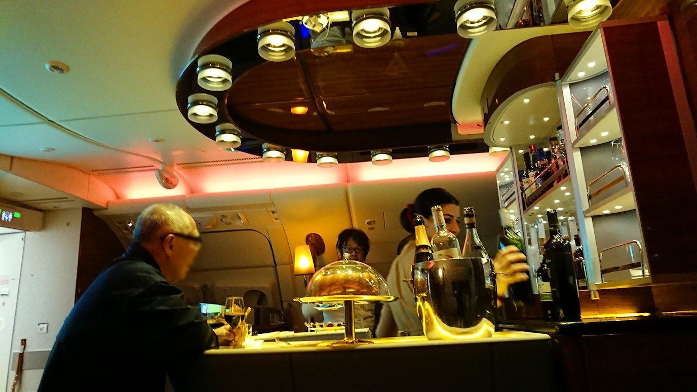 ドバイ国際空港から関西国際空港に向けて飛んでいる飛行機の機内ラウンジで盛り上がる