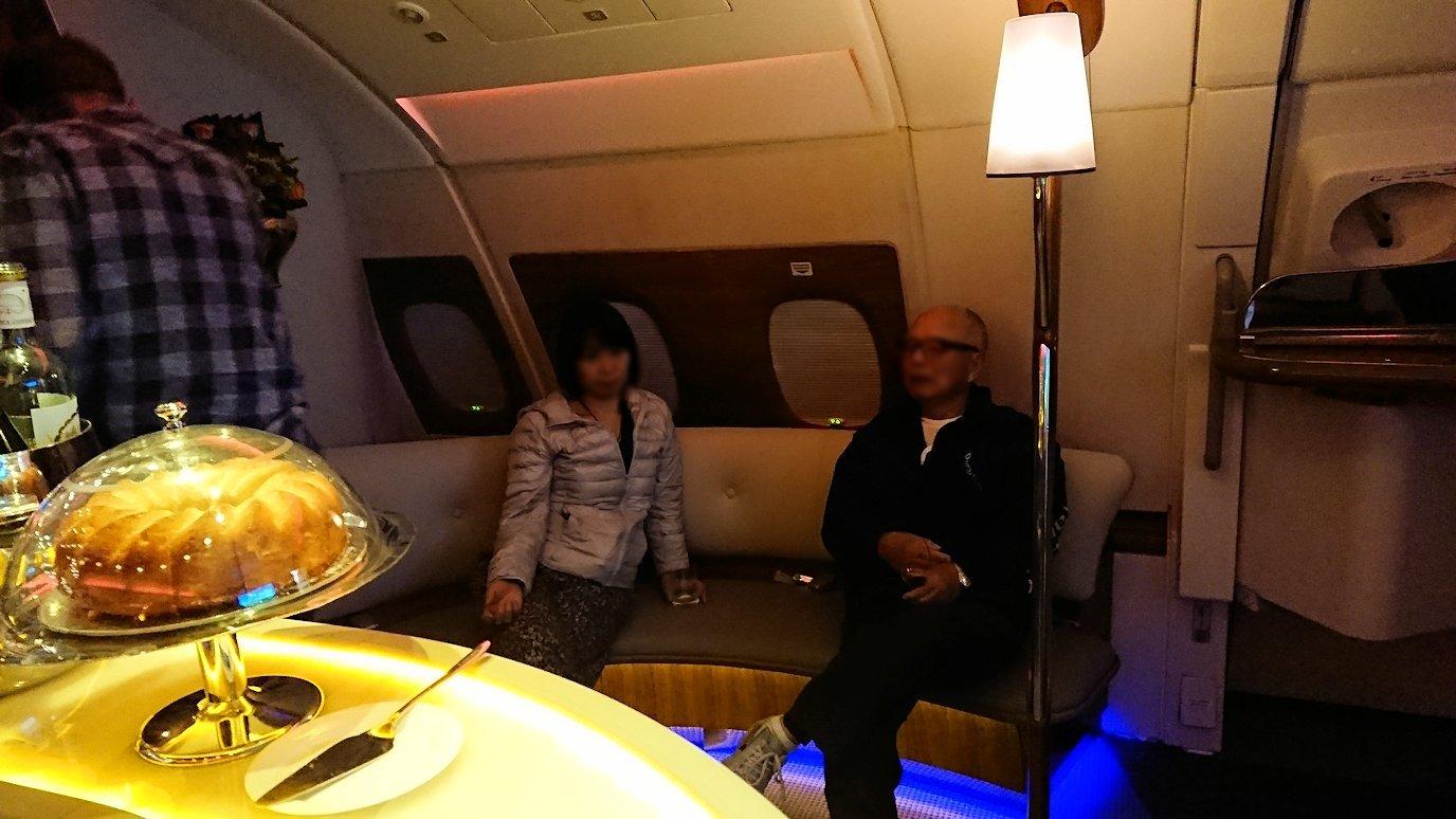 ドバイ国際空港から関西国際空港に向けて飛んでいる飛行機の機内ラウンジで盛り上がる2