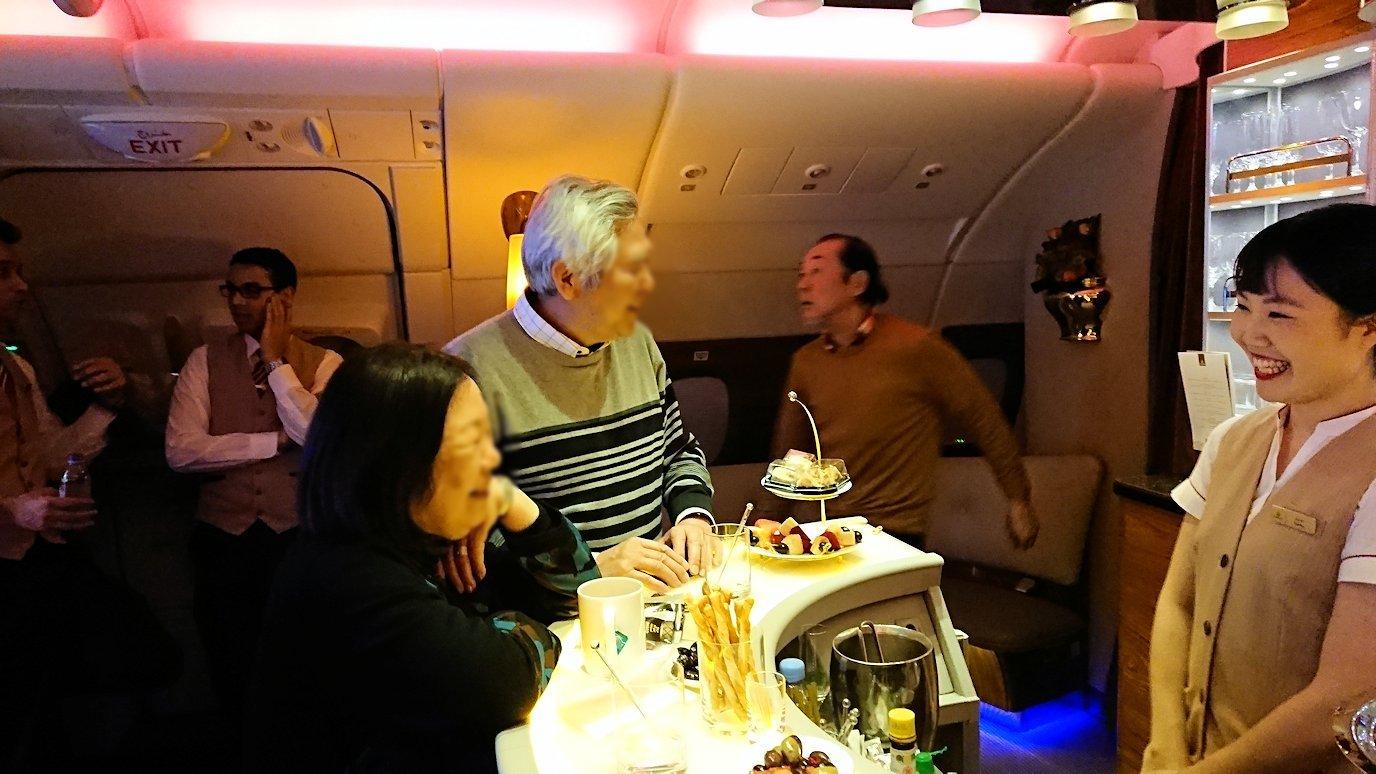 ドバイ国際空港から関西国際空港に向けて飛んでいる飛行機の機内ラウンジで盛り上がる8
