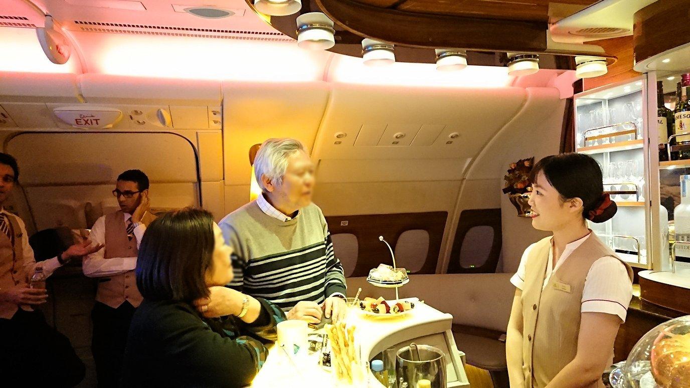 ドバイ国際空港から関西国際空港に向けて飛んでいる飛行機の機内ラウンジで盛り上がる9