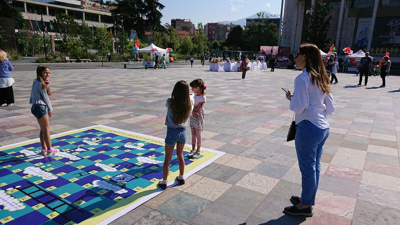 アルバニアで首都ティラナのスカンデルベグ広場ですごろくで遊ぶ子を8