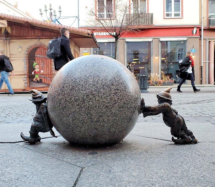 石を押し合う小人像