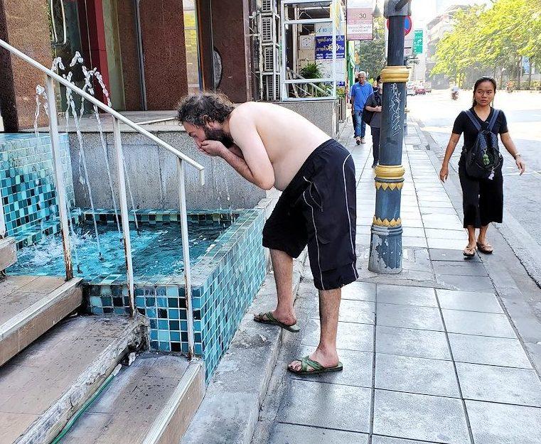 バンコク市内の「キングパワー・マハナコーンビル」近くの噴水で顔を洗う白人のオジサンを眺める