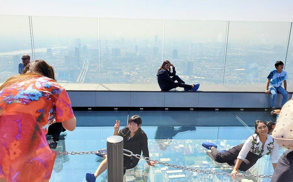 「キングパワー・マハナコーンビル」の屋外展望デッキにある、足元がガラスで透けるスカイウォークの上に座る人達