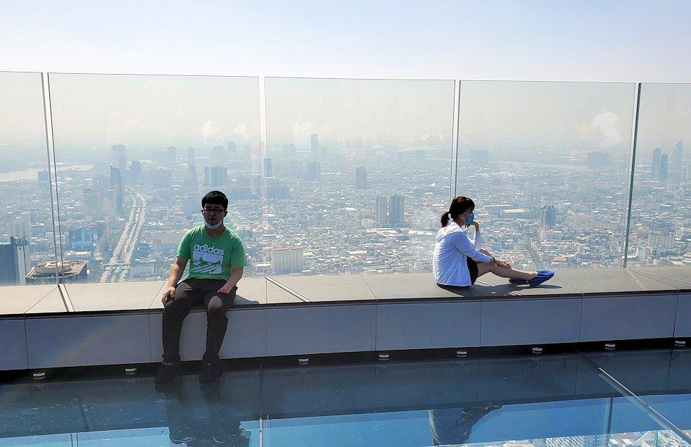 キングパワー・マハナコーンビルの屋外展望台にある、足元がガラスのスカイウォークで楽しむ人達