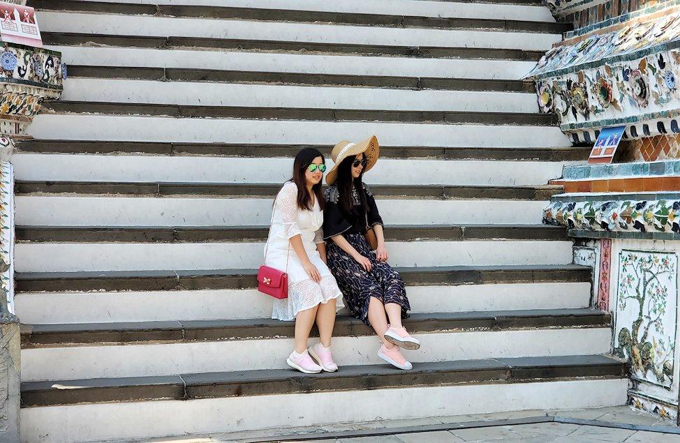 バンコク市内にあるワット・アルン寺院の階段に腰掛ける女性達