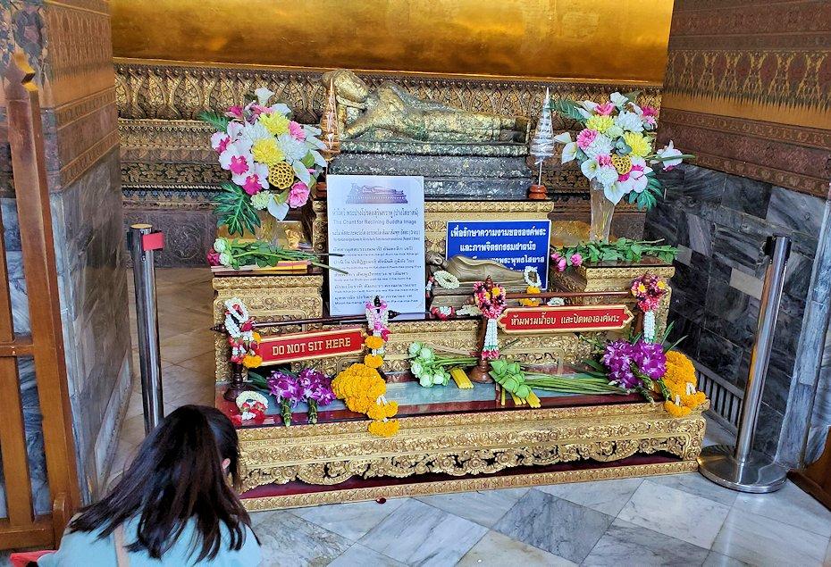 バンコク市内のワットポーで黄金の寝釈迦像のお供え物
