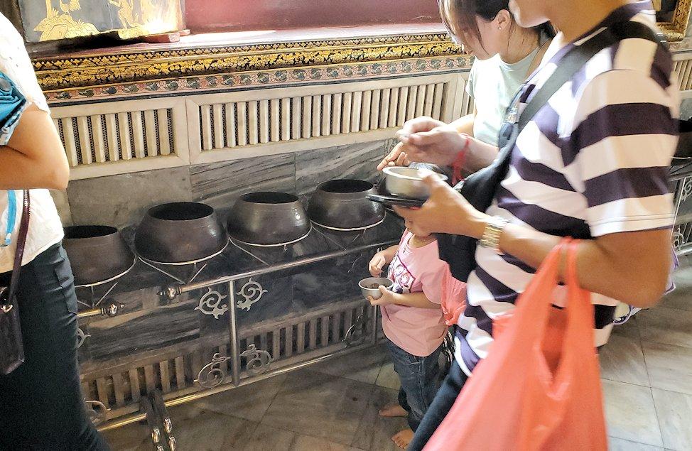 バンコク市内のワットポーで黄金の寝釈迦像のある建物にで売られていたコインを托鉢に入れる