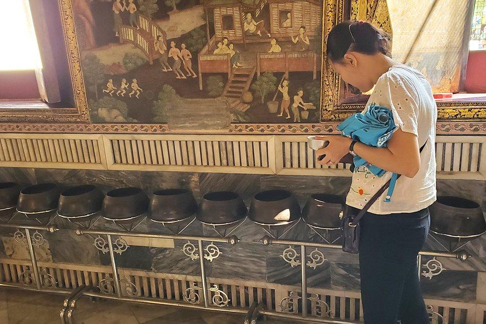 ワット・ポー内の涅槃像の裏で托鉢にお金を入れる人
