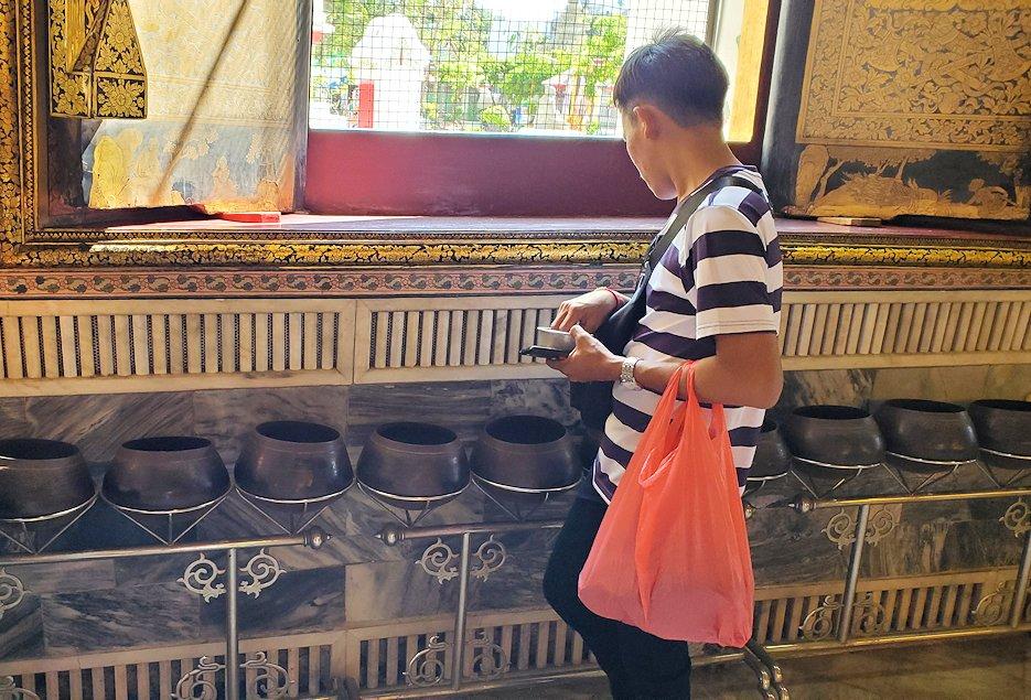 ワット・ポー内の涅槃像の裏で托鉢にお金を入れる人-2