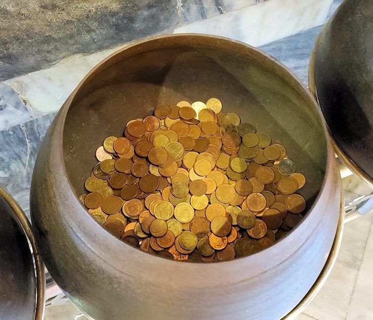 ワット・ポー内の涅槃像の裏で托鉢にお金を入れる人が入れたコイン